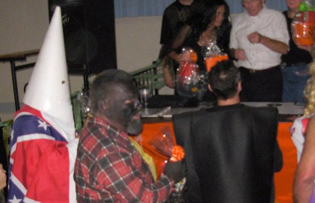 A person wears a white cone with eyeholes on his head, and a Confederate flag is draped over his shoulders. He leads a White Caucasian man wearing black makeup on his face and hands, who is wearing a plaid shirt.