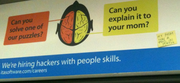 A public transit ad shows a brain with two hemispheres. A box pointing to the left hemisphere asks, 'Can you solve one of our puzzles?' A box pointing to the right hemisphere asks, 'Can you explain it to your mom?' Text at the bottom says, 'We're hiring hackers with people skills. itasoftware.com/careers' There is a real yellow sticky note stuck on to the ad that says, 'My mom has a PhD in math.'