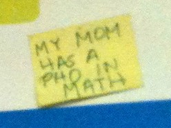 Close up of yellow sticky note that says, 'My mom has a PhD in math'