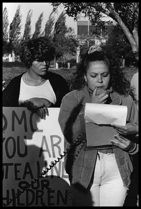 A woman of color reads from a sheet of paper while another woman of color stands beside her.